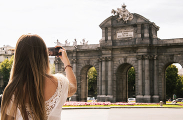 "Picture of a young blonde woman taking photos of the ""Puerta de Alcala"" in Madrid with her smart-phone."