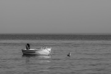 black and white photography of sky and sea at sunrise with a little old boat
