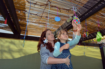 Jewish woman and child decorating their family Sukkah