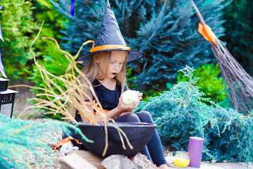 Wall Mural - Happy little girl wearing witch costume on Halloween outdoors