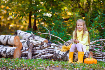 Wall Mural - Adorable little girl with a pumpkin for Halloween outdoors at