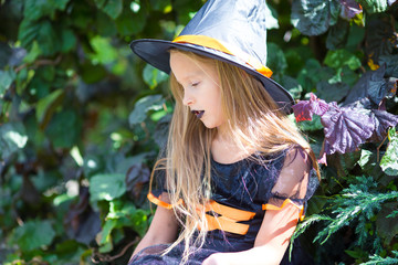 Wall Mural - Adorable little girl wearing witch costume with broom on