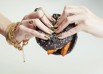 hands of rich woman with golden manicure and jewelry holding