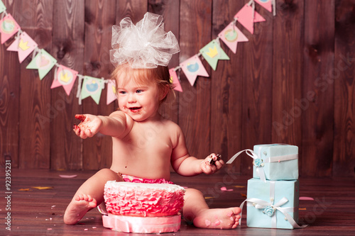 Baby Girl 1 Year Old Eating Birthday Cake Over Wooden Background