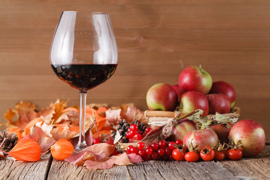 Fall wine in glass on rustic wooden background
