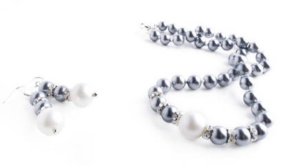 Pearls necklace and earrings on white