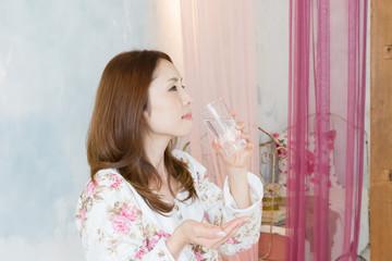 薬を飲むパジャマ姿の女性