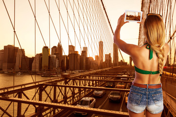 Blond tourist girl taking photo in Brooklyn Bridge