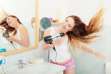 long haired woman drying hair in bathroom