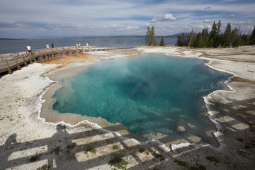 Steaming aqua hot spring, with people on boardwalk, Yellowstone.