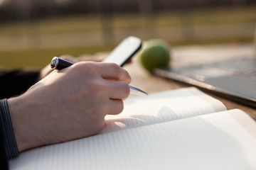 Man using smartphone and writing notes in personal notebook.