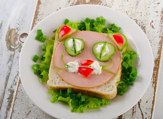 Breakfast with a smiling toast and fresh vegetables.