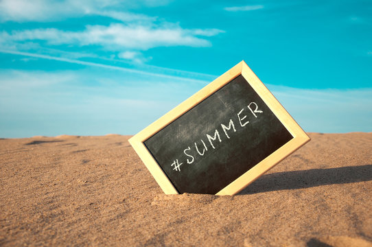 closeup of a chalkboard with a wooden frame and the word #summer written in it, placed on the sand of a beach