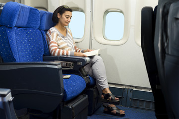 caucasian woman passenger in airplane reading a book on the seat