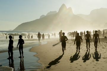 Silhouettes of people walking along golden sunset shores of Ipanema Beach Rio de Janeiro Brazil