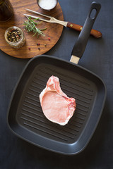 Raw pork rib chops on the grill frying pan with spices and herbs