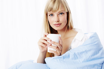 Young woman with coffee and duvet, portrait