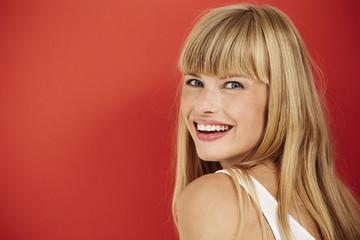 Joyful woman smiling on red background, portrait