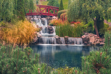 Red old wooden bridge with waterfall