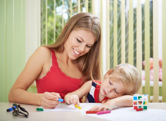 Painting family. Attractive young mother coloring picture with small cute girl sitting at the table indoors.