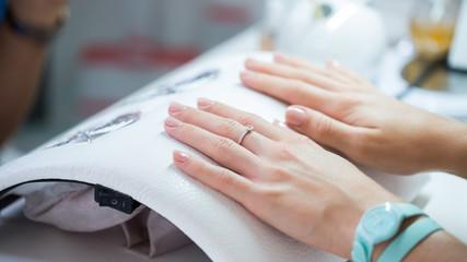 Woman hand on manicure treatment in beauty salon.