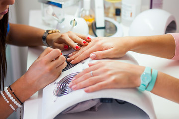 Woman hand on manicure treatment in beauty salon.