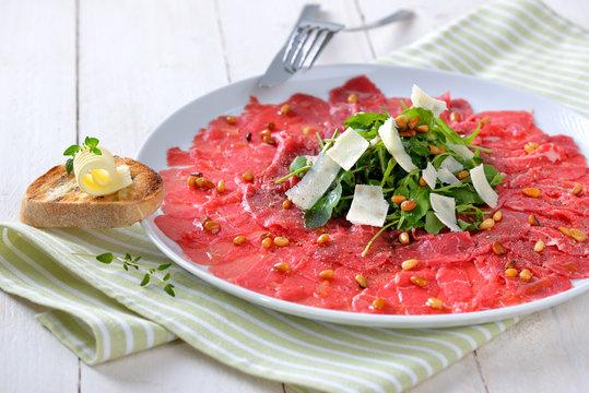 Feines Carpaccio vom Rinderfilet mit Rucola, Parmesan und gerösteten Pinienkernen