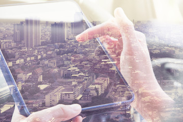 Using digital tablet double exposure and and cityscape background. Business  technology concept.