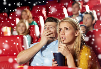 friends or couple watching horror movie in theater