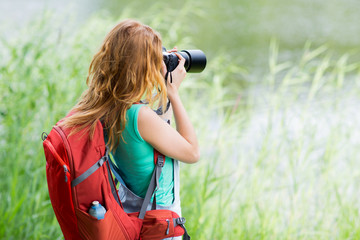 young woman with backpack and camera outdoors