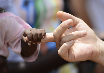 Black Baby and White woman holds hands with a little baby native African girl, in Bamako, Mali. Peace on earth symbol. A beautiful shot with lots of possible background symbols. No to Racism!