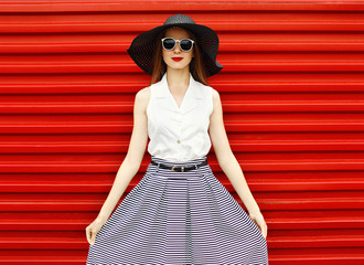 Fashion portrait of beautiful woman wearing a black straw hat, s