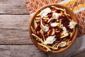 Canadian cuisine: poutine with sauce and cheese. horizontal top view