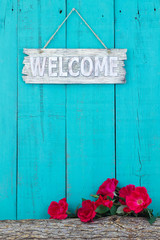 Welcome sign hanging hanging on fence by rose covered log