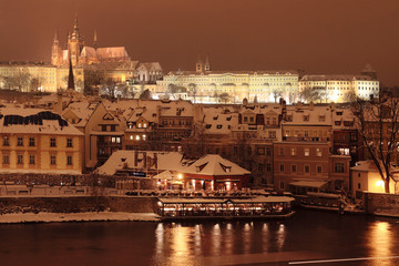 Night romantic colorful snowy Prague gothic Castle with Charles Bridge, Czech Republic
