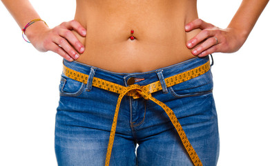 a slender young woman in jeans with a tape measure after a succe