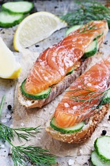 Sandwich with smoked salmon and cucumber on grilled baguette . Selective focus.