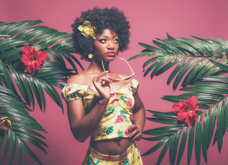 Tropical Afro American Pin-up Holding Sunglasses. Against Pink B