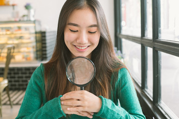 Smiling beautiful teenage asian girl with magnify search somethi