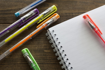 multicolored ballpoint pens and notebook