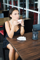 Girl in cafe drinking a coffee