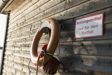 Orange life belt hanging wooden shed sign