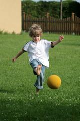Kleinkind spielt Ball im Garten