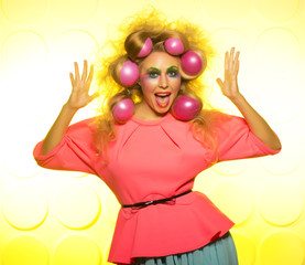 Cheerful girl with bright makeup and hair balls on a yellow background