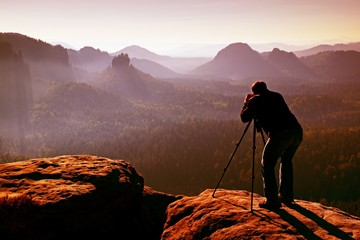 Professional on cliff. Nature photographer takes photos with mirror camera on peak of rock. Dreamy blue fogy landscape,