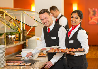 Catering service employees filling buffet at restaurant or hotel