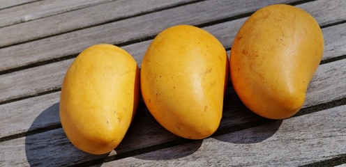 Three ripe yellow mangoes on a wooden table