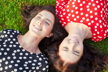 Beautiful twin sisters lying on the grass