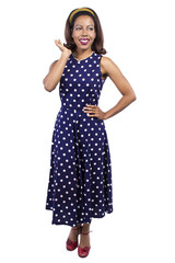 Black female wearing a blue vintage polka dot dress on a white background