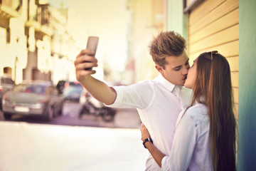 In love teenagers doing a selfie while kissing
